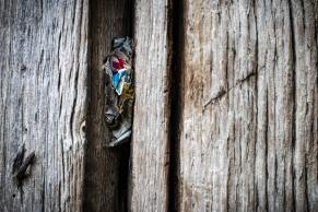 Jemand hat Bonbonpapier in eine Ritze zwischen den Balken gesteckt. - Someone put candy wrappers in a crack between the bars.